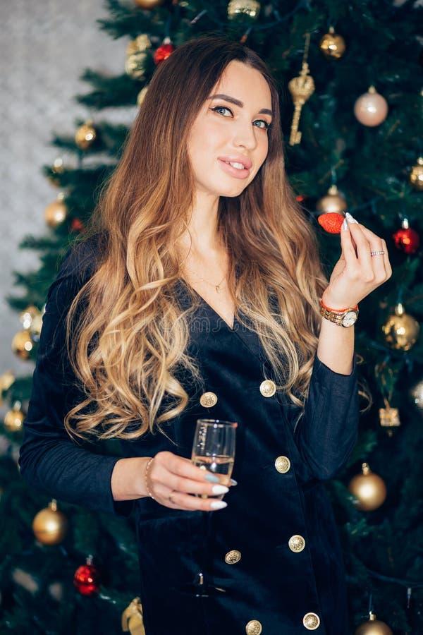 党,饮料,假日,庆祝,晚礼服的微笑的妇女与玻璃champagnenear圣诞树 免版税库存照片