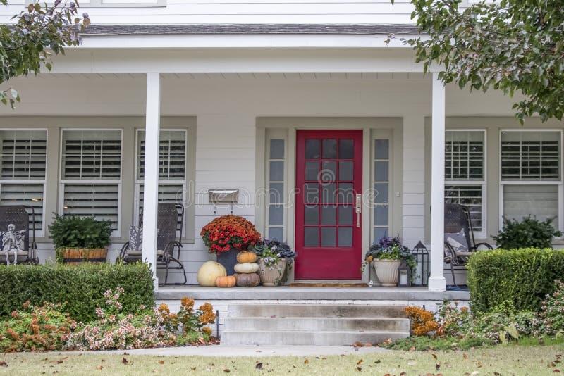 入口和门廊对俏丽的房子有秋天和万圣节装饰的和吹在风-遏制呼吁的秋天叶子 免版税图库摄影