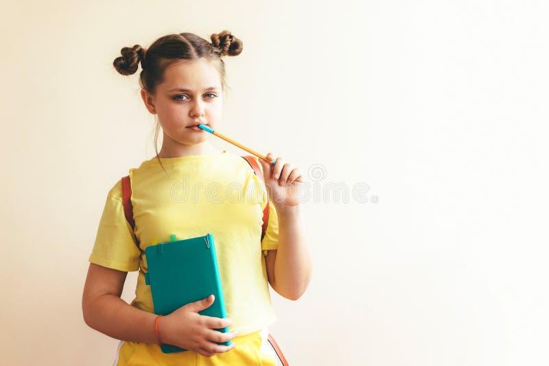 入学年龄的女孩与一个书、笔和学校背包的在黄色运动服 图库摄影