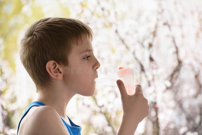 入学年龄的男孩在呼吸面具吸入器的在开花的树背景  r ?? 免版税库存照片