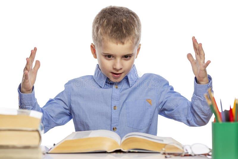 入学年龄的逗人喜爱的男孩与坐在桌上的一张惊奇的面孔的 r 免版税库存图片