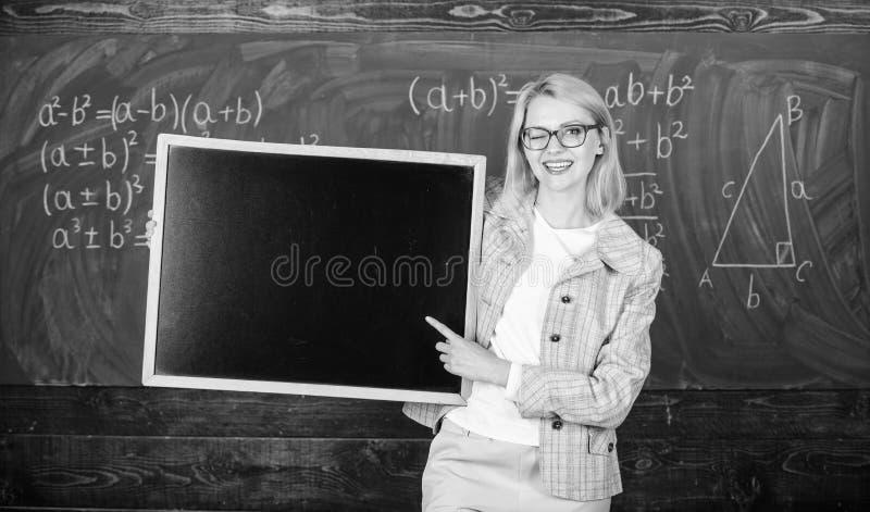 入学生的学校信息 老师展示学校广告 老师妇女举行黑板空白 库存照片