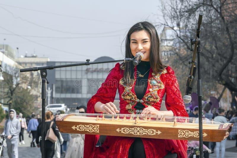 全国哈萨克人服装的美女弹奏民间乐器Zhetygen  库存图片