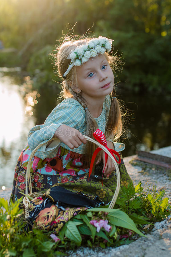 全国礼服和花花圈的俄国女孩坐在河的河岸的一个夏天晚上 免版税库存照片