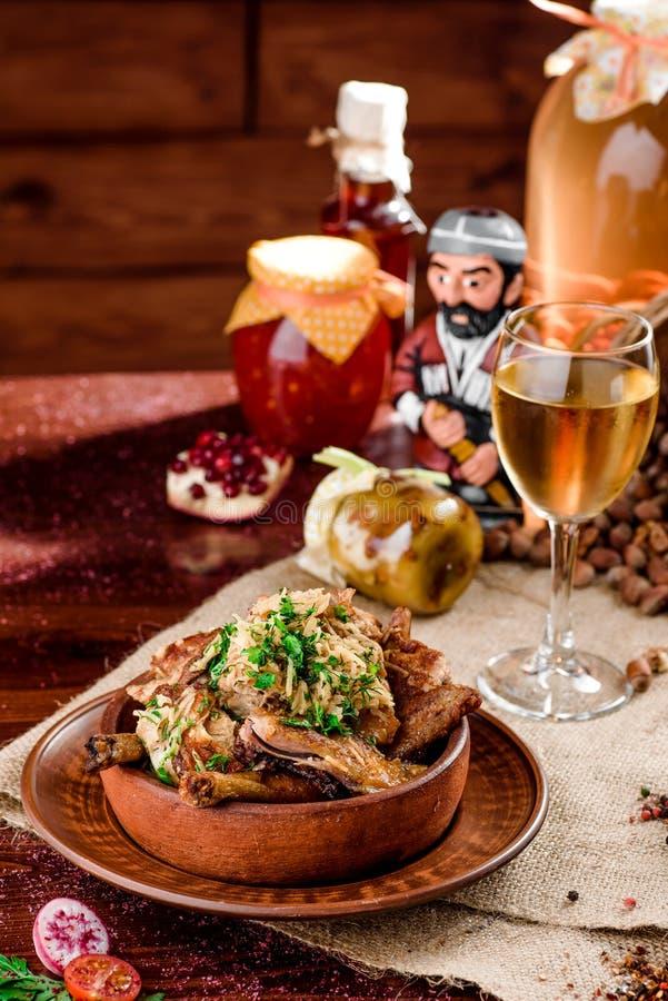 全国英王乔治一世至三世时期烹调 在一块棕色板材和一杯的鸡大腿在一块粗麻布的白酒在一张木桌上 免版税库存照片