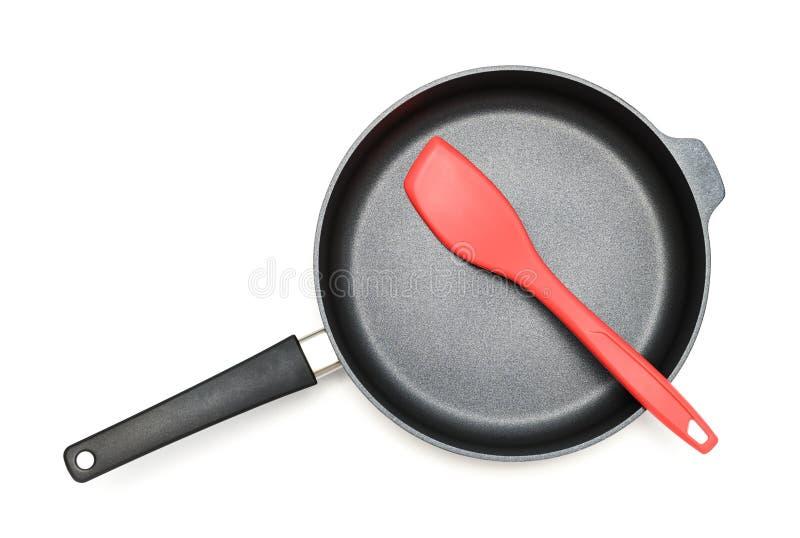 全新的暗淡黑不锈钢平底锅和硅小铲在白色背景 免版税库存照片