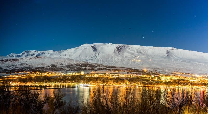 全景在阿克雷里市夜在与雪的冬天在nig 免版税库存照片