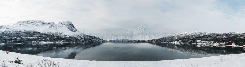 全景挪威Rombaksfjorden,与山的海湾视图在边在一个春日与看风景的冬天 库存图片