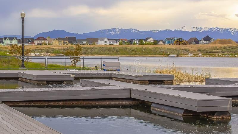 全景有木甲板的框架俯视在象草的岸之外的湖和长凳房子 库存图片