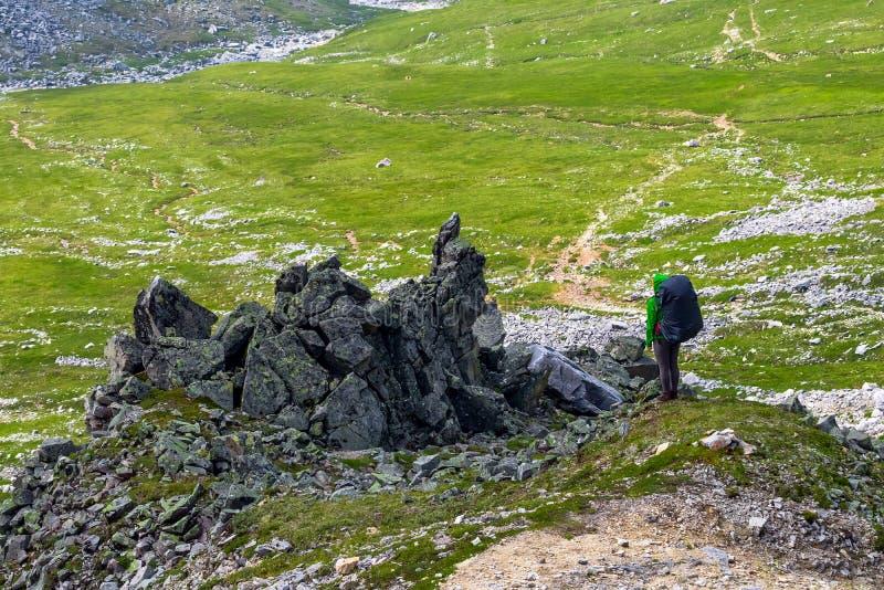 全景有站立在山谷的背景,旅行体育生活方式的峭壁的背包的妇女徒步旅行者 免版税库存照片
