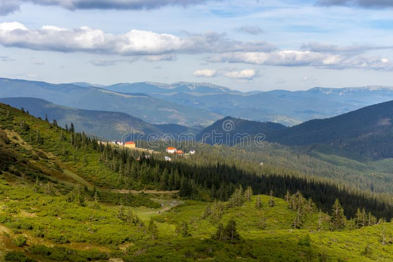 全景用云彩的村庄和阴影在绿色森林谷的山景 在透视的喀尔巴阡山脉 免版税库存图片