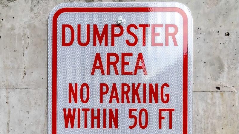 全景的框架关闭读大型垃圾桶地区禁止停车对一个混凝土墙标志 免版税图库摄影