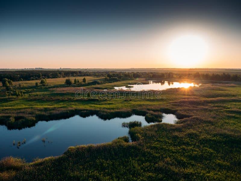 全景自然风景鸟瞰图与沼泽地、平原与植被和湖的日落的 图库摄影