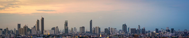 全景高层办公大楼曼谷的市中心 在黎明,从天空的光橙色 免版税库存照片