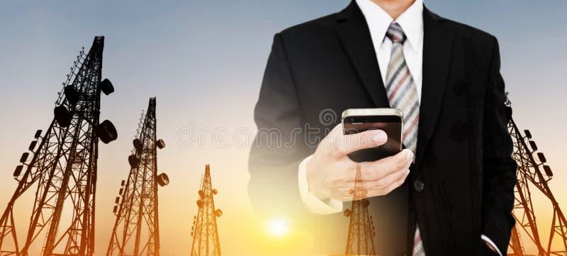 全景,商人使用有电信的手机耸立与电视天线和卫星盘在日落 免版税库存图片
