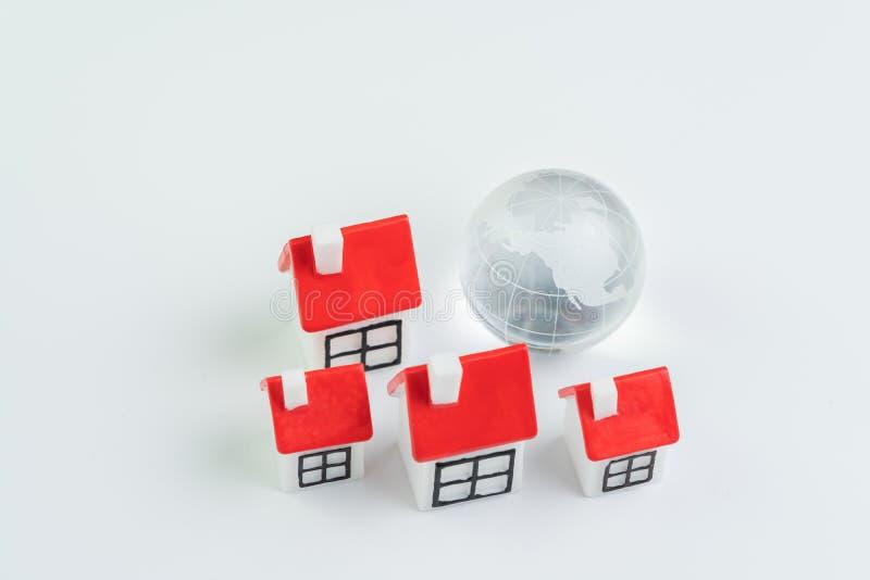 全球性或世界物产、房子和房屋贷款、不动产或者抵押贷款概念,与地图的装饰玻璃地球与小组  库存照片