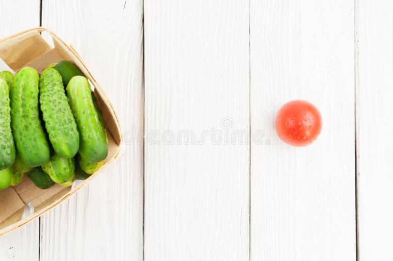 全部在柳条筐和唯一红色成熟蕃茄的新鲜的绿色黄瓜在老木背景 图库摄影