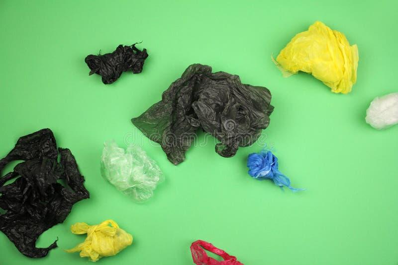 全部在绿色背景,大生态问题的被弄皱的半新塑料袋不同颜色 库存照片