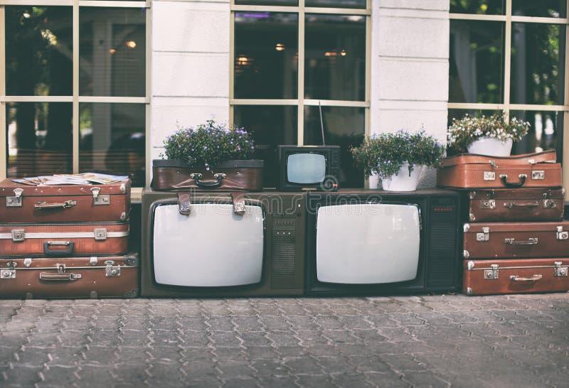 全部葡萄酒与老减速火箭的手提箱和房子植物的电视机装饰启发的罐的在街道上 库存图片