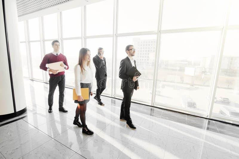 全长一起走小组愉快的年轻的商人走廊在办公室 步行队 免版税库存照片