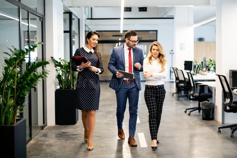 全长一起走小组愉快的年轻的商人走廊在办公室 免版税库存图片