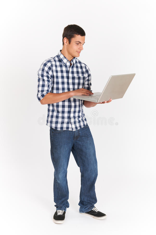 全长使用膝上型计算机的被删去十几岁的男孩 图库摄影