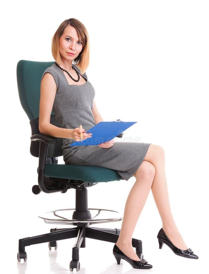 全长女商人坐拿着剪贴板的椅子是 图库摄影