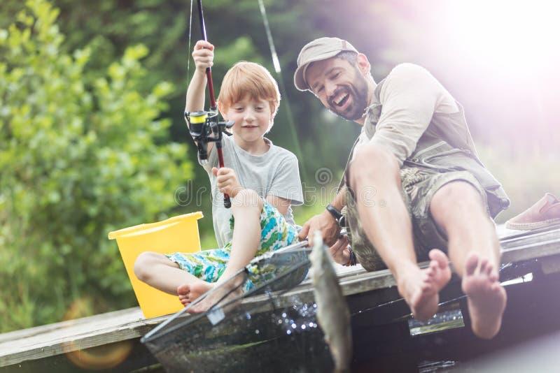 全长微笑的父亲和儿子捉住的鱼在蝴蝶鱼网方面 免版税库存图片