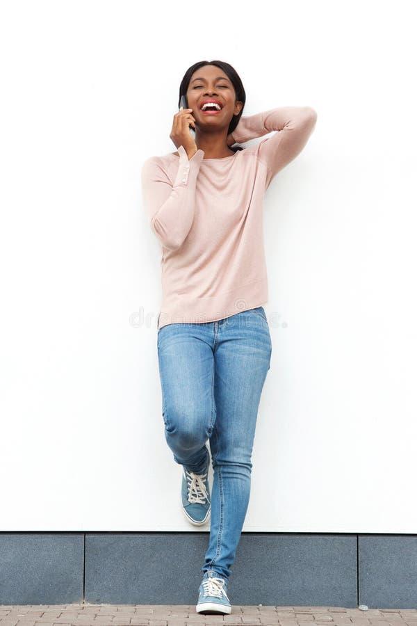 全长愉快的年轻黑人妇女身分对白色墙壁谈话在手机 库存图片