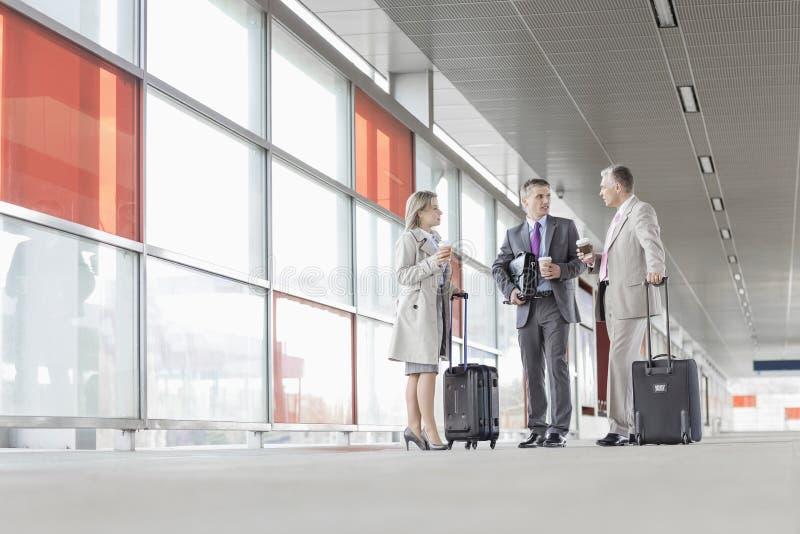 全长有行李的买卖人谈话在铁路平台 免版税图库摄影