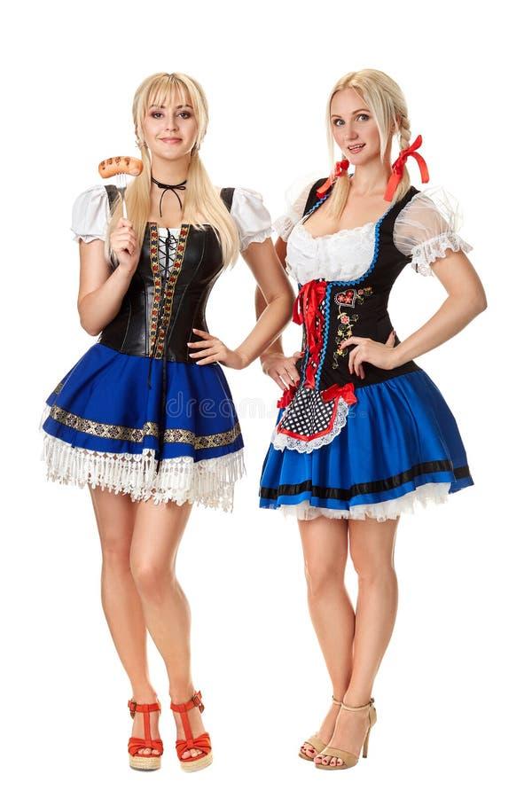 全长的画象有拿着啤酒杯的传统服装的两名白肤金发的妇女的被隔绝在白色背景 免版税库存图片