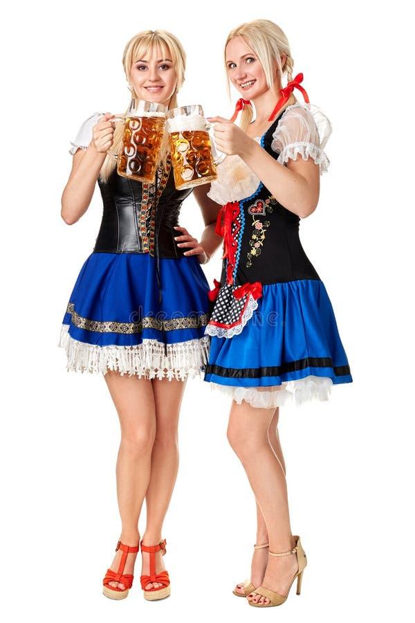全长的画象有拿着啤酒杯的传统服装的两名白肤金发的妇女的被隔绝在白色背景 库存照片