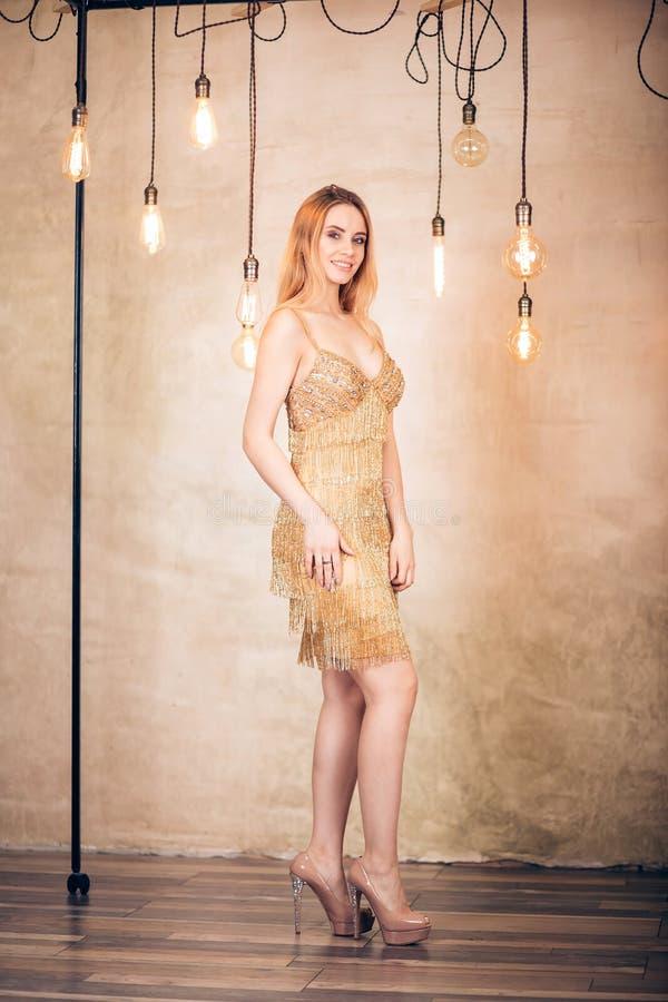 全长短的金礼服的画象典雅的白肤金发的妇女在演播室 党,假日,庆祝,新年,圣诞节 库存照片