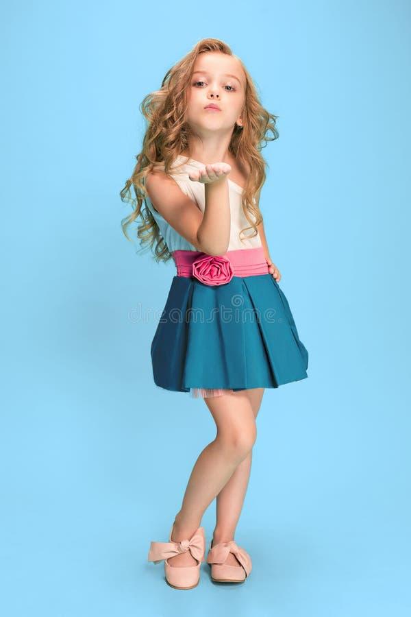 全长站立和摆在蓝色背景的礼服的美丽的小女孩 免版税库存照片