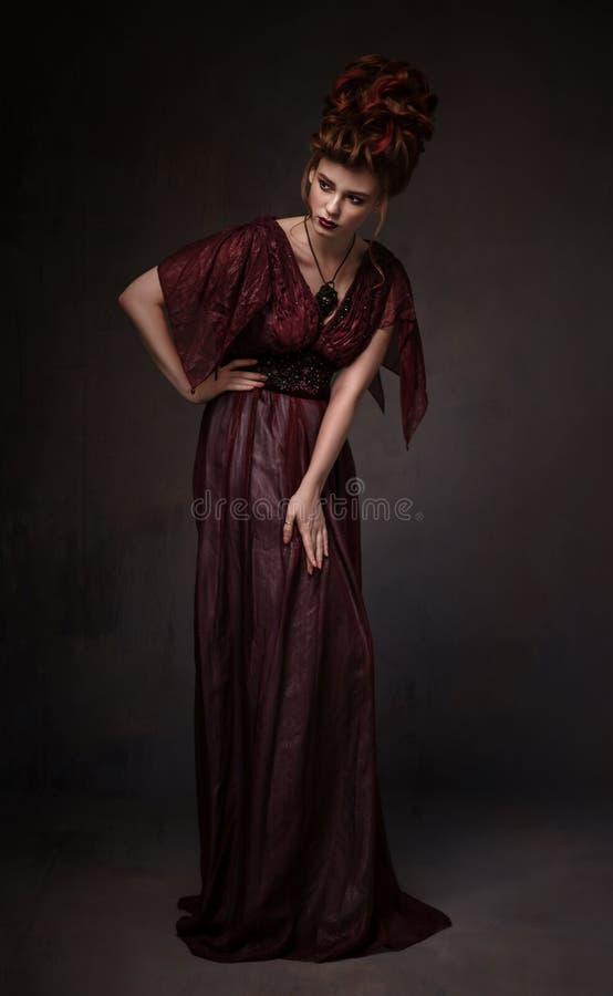 全长观点的有巴洛克式的发型和平衡的褐红的礼服妇女 免版税库存照片