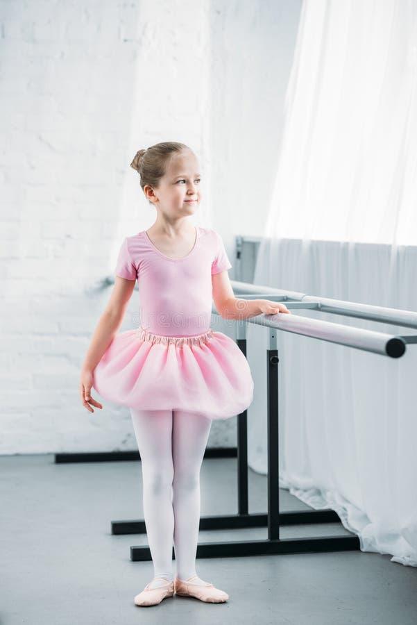 全长观点的看桃红色的芭蕾舞短裙的美丽的矮小的芭蕾舞女演员  免版税库存照片