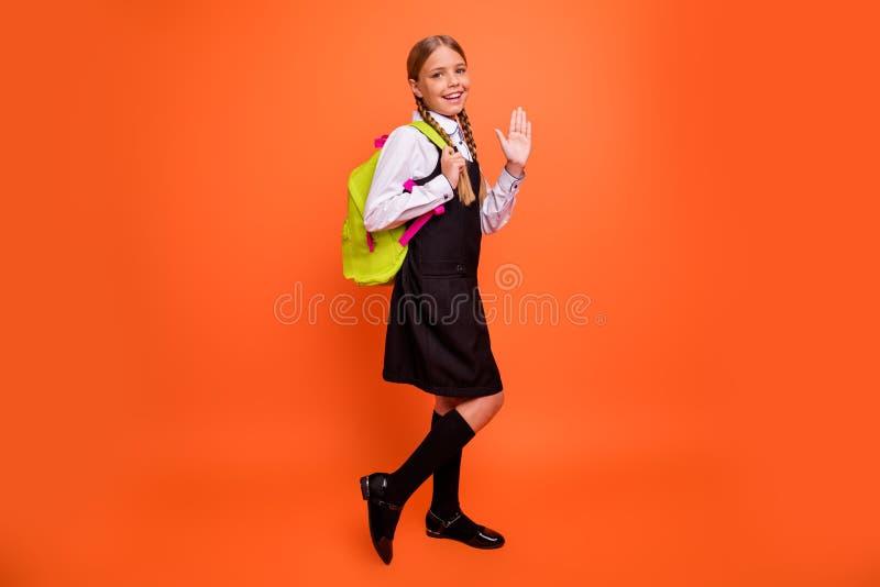 全长身体尺寸观点的她她回到学校的好可爱的快乐的爽快确信的努力青春期前的女孩 库存照片