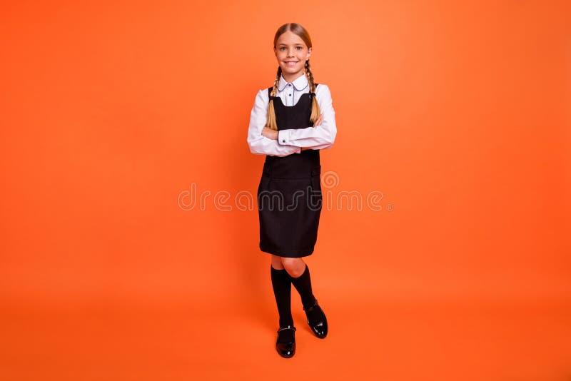 全长身体尺寸观点的她她好可爱的可爱的迷人的快乐的爽快美满的青春期前的女孩交叉双臂 免版税图库摄影