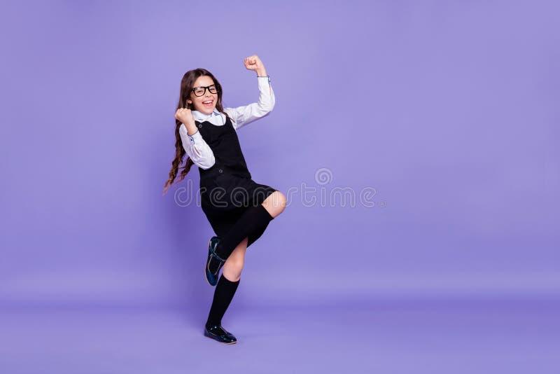 全长身体尺寸观点的好可爱的快乐的爽快高兴的确信的成功的有波浪头发的青春期前的女孩 免版税库存照片