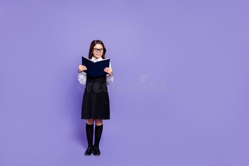 全长身体尺寸观点的好的有吸引力的快乐的举行内容努力聪明的有波浪头发的青春期前的女孩  免版税库存图片