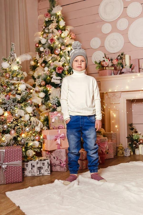 全长身分的男孩学龄前儿童在圣诞树旁边的充分的高度 人们和圣诞节 免版税库存图片