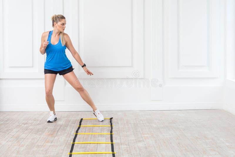 全长黑短裤的运动的美丽的年轻运动白肤金发的妇女和蓝色上面与速度皮带的心脏锻炼打开 免版税库存图片