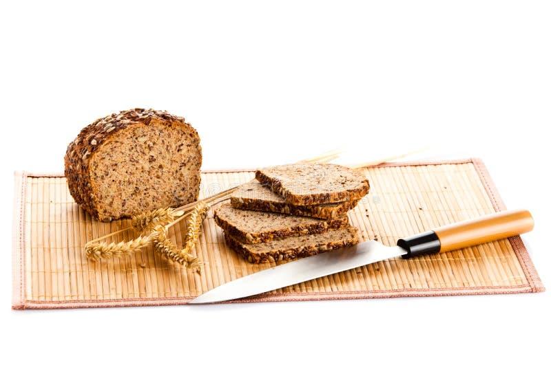 全麦面包切口大面包到在木面包板的切片里 库存图片