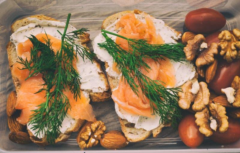 全麦面包用乳酪和三文鱼在塑胶容器 莳萝和杏仁用西红柿 健康三明治 图库摄影