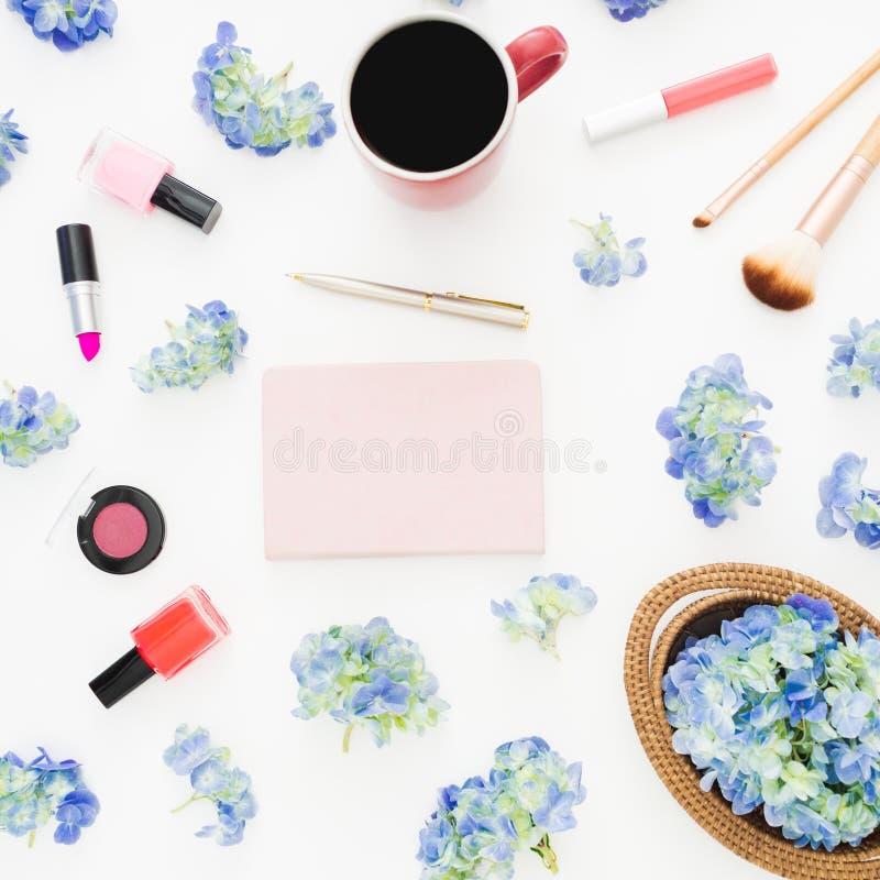 八仙花属花的构成与女性化妆用品、笔记本和杯子的在白色背景的咖啡 平的位置,顶视图 图库摄影
