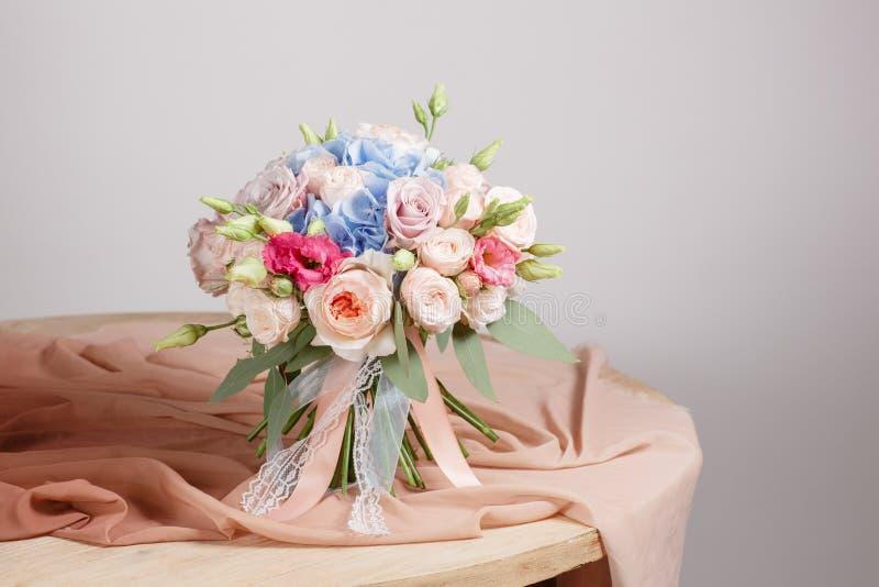 八仙花属富有花束 葡萄酒植物的背景、五颜六色的玫瑰、古色古香的剪刀和一条绳索在一张老木桌上 免版税库存照片