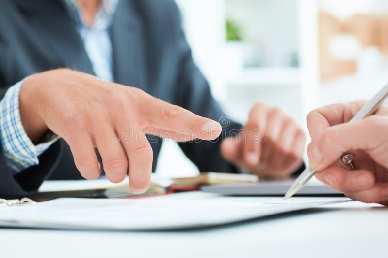 公上司在办公室建议他的雇员标志一个合同 商人指向它的地方 免版税库存图片