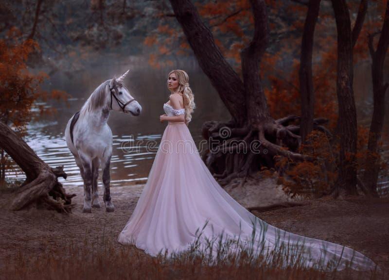 公主在森林里在一件长的葡萄酒礼服遇见了一只独角兽有柔和的构成的白肤金发的女孩,穿戴与 免版税库存图片