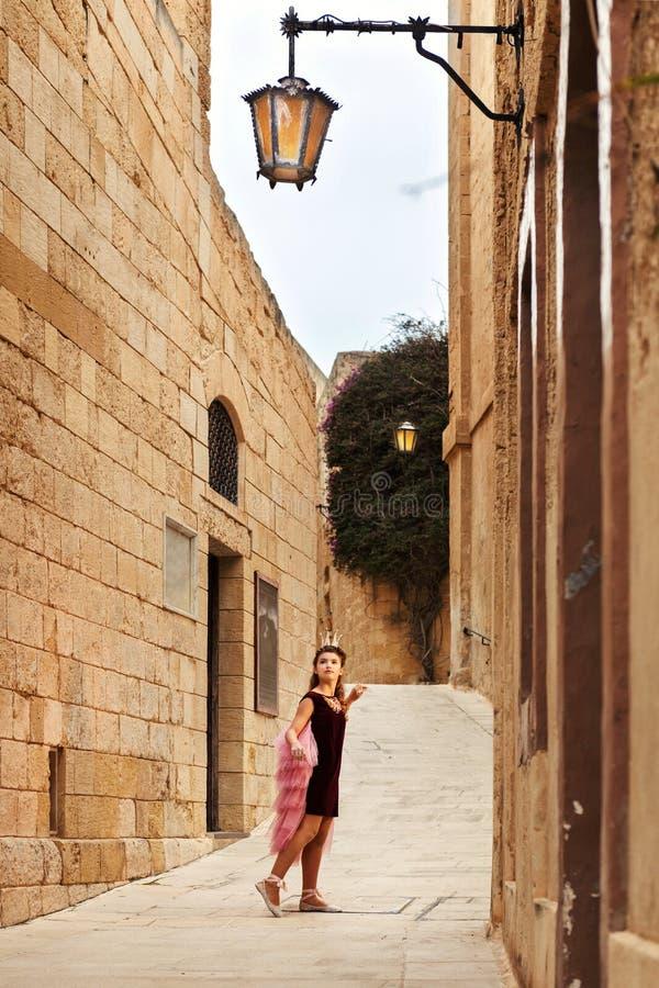 公主女孩在看古板的灯笼的黄色石头城堡镇的老街道失去 免版税库存图片
