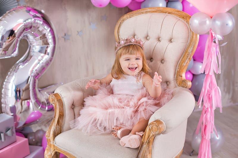 公主庆祝生平事件的女婴穿金黄冠和桃红色通风礼服 摆在淡色演播室射击的逗人喜爱的女孩 库存照片